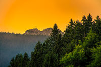 View at the hiking destination at the Kampenwand cross at a wonderful golden hour light from far away at the peak of the alpine mountain peak.