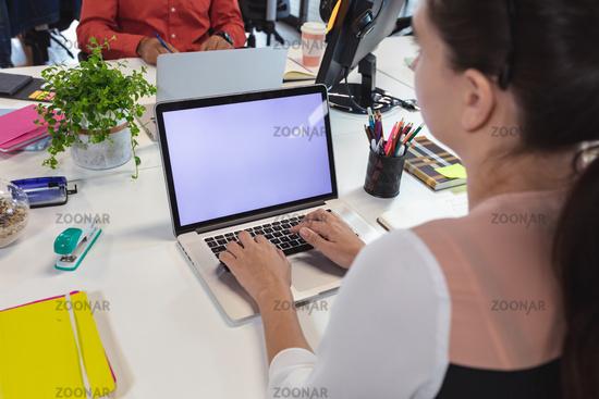 Caucasian female creative worker sitting at desk using laptop