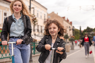 The stylish little girl rides a scooter in the city