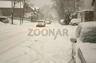 car drives on a snowy street in winter