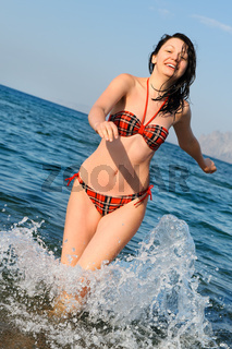 The joyful woman runs on sea water