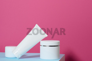 jar and empty white plastic tubes for cosmetics on a pink background. Packaging for cream, gel, serum, advertising and product promotion