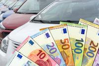 Kaufpreis Autokauf - Euroscheine mit PKWs im Hintergrund
