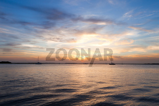 Sailing boat silhouette over sunset sky