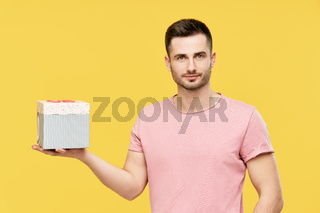 Handsome young man holding gift box on yellow studio background