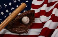 Baseball ball, bat and glove on American flag