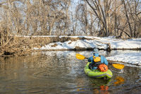paddling inflatable whitewater kayak on a river in winter
