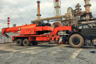 A heavy-duty truck crane with a folded boom stands on the industrial site of an oil refinery
