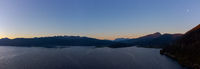 Epic drone panorama of mountain lake Walchensee in Bavaria, Germany in early dawn with alpine mountains andfull moon