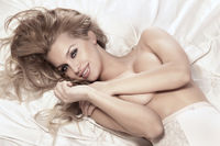 Portrait of smiling blonde woman lying in bed