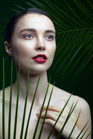 Romantic female on a background of palm leaves