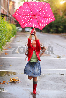 Child with polka dots umbrella wearing red rain boots