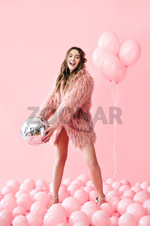 Trendy young woman have fun with party disco ball on pink balloons background