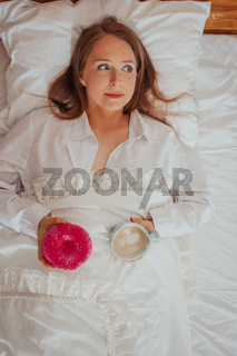 Drinking coffee and eating doughnut for breakfast in bed