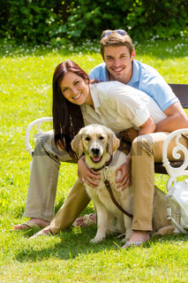 Couple sitting with golden retriever in park