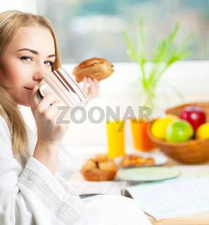 Beautiful calm young woman having morning coffee