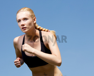 Beautiful young woman runner in nature