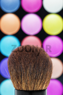 Makeup brush and shadows palette as background
