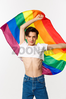 Vertical view of happy queer person in crop top and jeans waving raised rainbow flag, celebrating lgbtq holiday, standing over white background