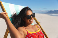 Smiling mixed race woman on beach holiday sitting in deckchair sunbathing