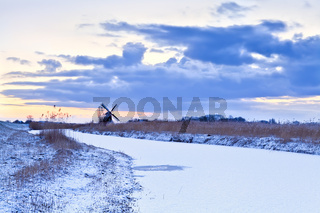 Dutch windmill in winter at sunrise