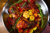 Fried chicken legs with various vegetables and spices