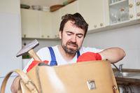 Heimwerker sucht unsicher nach Werkzeug