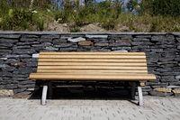 Bank / Gartenbank aus Holz vor Mauer aus Schiefer