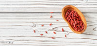 Dried goji aka. wolfberry seeds in wooden bowl and spilled on white boards desk near, view from above