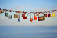 Various and heart colorful shaped love padlocks on a chain on a beautiful blue sky and sea background. Diverse locks as a symbol of togetherness and bonding.