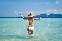 Happy woman have fun playing splashing water and enjoy her tropical beach vacation