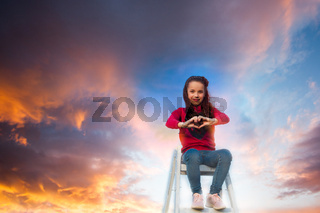 the happy girl on top of stepladder and shows heart