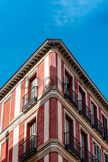 Low angle view of the corner of an old recently renovated residential building against blue sky
