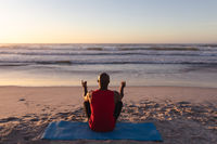 Rear view of senior african american man meditating and practicing yoga while sitting on yoga mat at