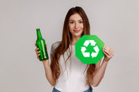 Woman holding glass bottle and green recycling sign, garbage sorting and environment protection.