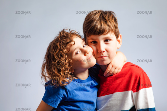 the cute little girl hugs her brother tightly