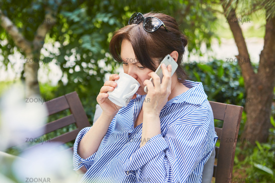 Business Frau trinkt eine Tasse Kaffee und telefoniert