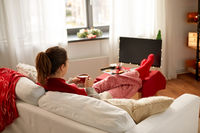 woman watching tv and drinking coffee on christmas