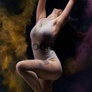 Gymnast in ecru bodysuit with colored dust around