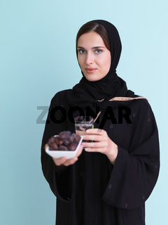 Modern muslim woman in abaya holding a date fruit and glass of water in front of her