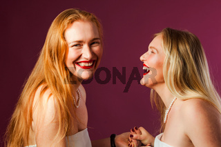 Two gorgeous women looking at each other, laughing