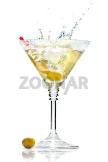Olive splashing on martini glass isolated