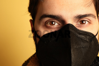 Close-up of man in black medical mask. Over yellow background.