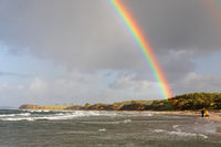 Regenbogen mit intensiven Farben über der Ostseeküste mit Brandung bei Sehlendorf