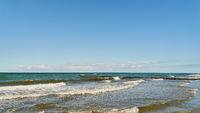 Blauer Himmel und weiße Wolken über Meer mit Wellen