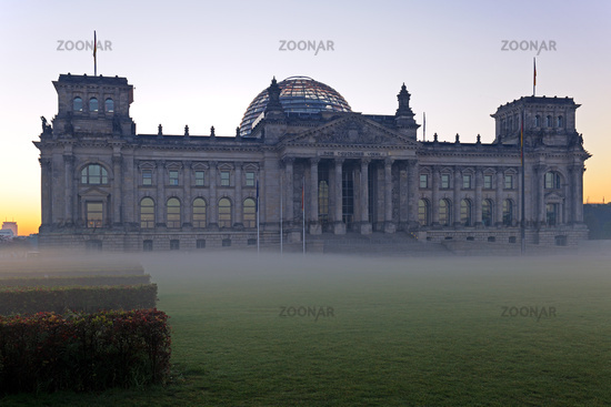 Reichstag in Berlin bei Sonnenaufgang und Bodennebel im Gegenlic