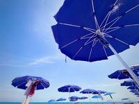 blue sun umbrellas open and arranged in rows at an Italian beach on a sunny summer