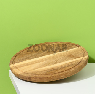 round wooden kitchen pizza board on a green background, utensils levitate, copy space