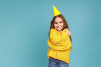 Little girl in party cone, embracing herself, celebrating her birthday, looking smiling at camera.
