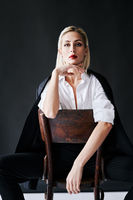 Fashion portrait of sensual trendy woman posing on retro chair against black studio background.